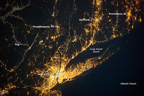 Satellite imagery showing the New York metropolitan area at night. Long Island extends to the east of the central core of Manhattan. New York City, Southern RI and CT, illuminated at night.jpg