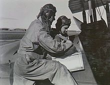 Two men in flying suits, one in the cockpit of a biplane and the other standing beside him