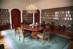 Ett rum med bilder på väggarna. I mitten av rummet finns ett träbord med stolar runt.