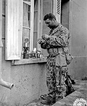 July 1944, US soldier wearing a two-piece herringbone twill (HBT) camouflage which was used by marines in the Pacific, but was quickly abandoned in the European theater because of the similarity to the uniform of the Waffen SS