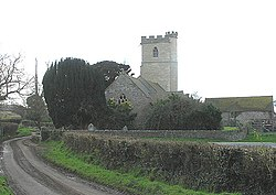 Stone building with prominent square tower. In the foreground is a road and wall.