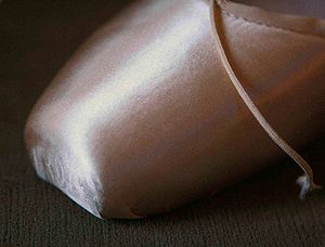 Pointe shoe - A pointe shoe's tightly stretched satin exterior exposes the shape of its underlying toe box.