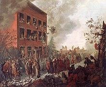 Brennende tre-etasjes hus, omgitt av en mobb.  Folk kaster ting ut av vinduene og eiendeler er spredt på gaten.
