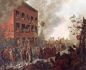 Burning three-story house, surrounded by a mob. People are throwing things out of the windows and belongings are scattered on the street.