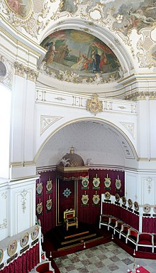 Frederick I's throne (bottom center) in the Ordenskapelle and its semidome. Coats of arms for members of the Order of the Golden Eagle line the walls above their seats.