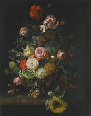 Still life of roses, tulips, a sunflower and other flowers in a glass vase with a bee, butterfly and other insects upon a marble ledge