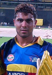 Ravindra Jadeja, who is seen wearing a yellow jersey and carrying his batting pads.