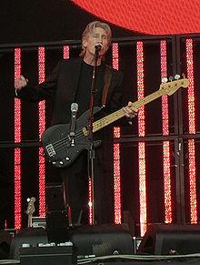 Roger Waters, dressed in black, playing a bass guitar and speaking into a microphone. Behind him are several red vertical video panels.