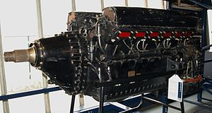 A front left view of a large black-painted aircraft piston engine. The engine is backlit by a window.