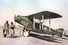 Two men in long leather coats and leather helmets stand in front of a biplane in RAF colours.
