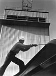 Sailor adjusts aerial of plane in front of control tower at NATC, Corpus Christi, Texas HD-SN-99-02496.jpg