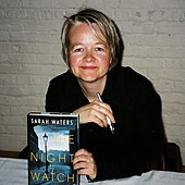 Image of a woman with short blond hair seated at a table holding a pen and a book cover to the camera