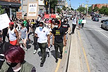 Protesters wearing COVID masks marching down a Baltimore street on May 30