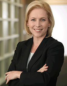"A portrait shot of a smiling, middle-aged Caucasian female (Kirsten Gillibrand) looking straight ahead. She has chin-length blonde hair, and is wearing a dark blazer with a grey top; on her left lapel is a gold pin that reads ""United States Senator"". She is placed in front of a dark background."