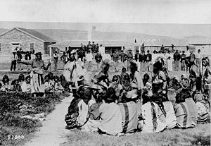 "Shoshone - ""Shoshone at Ft. Washakie, Wyoming Native American reservation. Chief Washakie (at left) extends his right arm."" Some of the Shoshones are dancing as the soldiers look on, 1892"