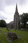 A large Gothic Revival church with an elaborate west tower surmounted by a spire supported by flying buttresses