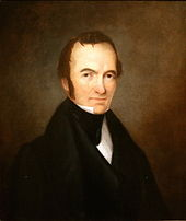 Portrait of a man with receding hairline and long sideburns, wearing an 1840s-style suit.