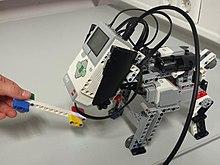 Photo d'un robot Mindstorms EV3 en action. Il ressemble à un petit chien. Sa brique moteur remplace sa tête.