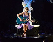 Taylor Swift, wearing a purple dress, plays a blue acoustic guitar while sitting on a stool