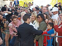 Tobey Maguire, in a suit, greets fans behind a security barrier. Most of the attendants hold cameras.