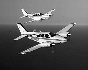 Beechcraft Baron - Two Baron 55s flying in formation with a 1980-built B55 nearest. E55 in background.