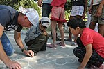 U.S. Air Force Staff Sgt. Calin Cronin draws a picture on the sidewalk with children during a visit to an orphanage in Krasnaya Rechka, Kyrgyzstan, Sept 120901-F-RO762-069.jpg