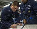 U.S. Navy Gas Turbine System Technician (Electrical) Seth Schaeffer signs his re-enlistment papers aboard the guided missile destroyer USS Gravely (DDG 107) May 17, 2013, in the Mediterranean Sea 130517-N-KA046-014.jpg