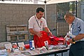 US Navy 061027-N-8909B-019 Cruz Ponce, the development and communications coordinator for American Red Cross, shows Aviation Structural Mechanic 1st Class Jose Campa some first aid equipment used for disaster relief.jpg