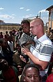 US Navy 080117-F-4089F-037 Builder 2nd Class Ryan Woolridge stands with children of the Bilate Charicho region of Ethiopia as they wait to attend the dedication of two new school buildings.jpg