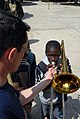 US Navy 090204-N-1688B-437 Musician 1st Class Duke Stuble lets students of Lycee Abdoulaye take turns learning about different musical instruments.jpg