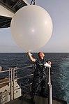 US Navy 100628-N-6362C-024 Aerographer's Mate 3rd Class Robert Dietrich launches a weather balloon off the fantail of the aircraft carrier USS Harry S. Truman (CVN 75).jpg