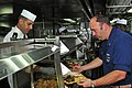 US Navy 111124-N-ER662-076 Chief Damage Controlman Joseph D. Kazmierski serves Sailors during Thanksgiving dinner.jpg