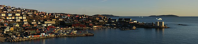 : Midnight sun panorama of the north-western part of the town Upernavik in Greenland. The viewpoint is a cliff near the soccer field with a south-western heading and was taken at 11:45 pm on August 8, 2007.