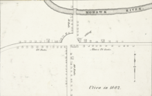 "A black-and-white map, depicting buildings and roads in simple, small black outlines. The text ""Utica in 1802"" is at bottom right."