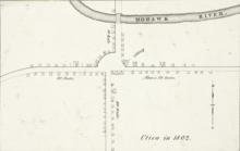 """Un mapa en blanco y negro, que muestra edificios y carreteras en pequeños contornos negros simples.  El texto """"Utica en 1802"""" está en la parte inferior derecha."""
