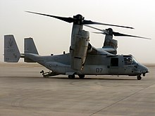 A side view of an MV-22 resting on sandy ground in Iraq during the day with its ramp lowered.