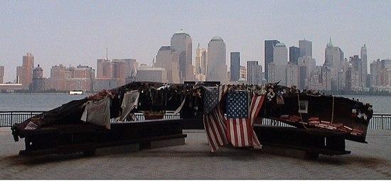 Vista en la que se puede apreciar en primer plano el monumento, hecho de algunos escombros, ubicado en Jersey City, New Jersey - Estados Unidos, y más atrás los edificios en Manhattan entre los cuales precisamente se alzaban las torres gemelas. (foto tomada en julio del 2007)