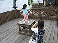 Woman taking picture of her daughter in a dock, Misaki, Japan; August 2009.jpg