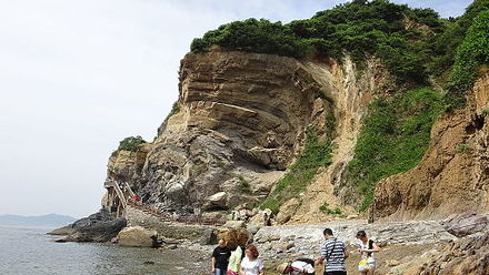 A wave-like sea cliff produced by coastal erosion, in Jinshitan Coastal National Geopark, Dalian, Liaoning Province, China Da Lian Guo Jia Di Zhi Gong Yuan 9-Hai Shi Ya .JPG