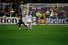 A man in a blue-and-red shirt with a football at his feet runs at a man in a white shirt. In the background, a man in a yellow shirt prepares for the ball to be kicked towards him.