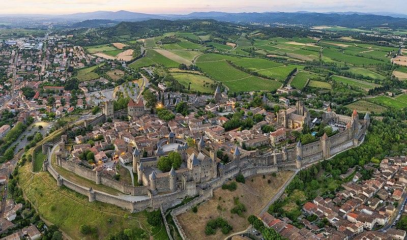 Foto aerea do cartelo de Carcassonne. Vê o castelo em sua totalidade e parte das construções do lado de fora do muro.