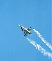 Jet aircraft performing rolls while climbing, revealing its underside. White smoke trail from each wing tip.