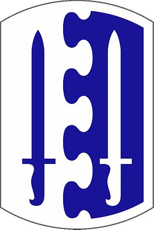 "2nd Brigade Combat Team, 1st Infantry Division - Shoulder sleeve insignia of the 2nd Infantry Brigade. The traditional infantry colours of blue and white.  Two bayonets reflect the number of the brigade.  During World War II a black and gold ""Airborne"" tab was worn over the insignia."