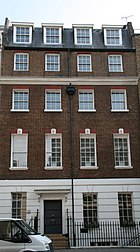 A terrace building. Its ground floor has plaster render inscribed to look like stone, the middle three are red brick, and the top is an attic. Each floor has four sash windows with a dozen or more panes each, except that the bottom floor has a door in place of the second window.