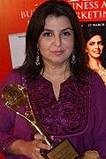 Portrait de Farah Khan, tenant un trophée dans les mains.