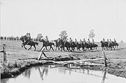 A large formation of soldiers riding horses pass a shallow dam