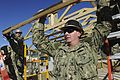 A Seabee holds up an A-frame as a hut is taken down. (8516135634).jpg