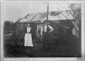 A hut with water tank on the left, and unidentified man and woman standing in front ATLIB 324488.png