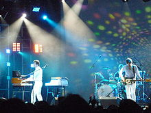 Three men play instruments on a brightly lit stage. Two of the men wear white clothing; they play a guitar and a keyboard respectively. The third man wears a black shirt and sits behind a drum set, playing.