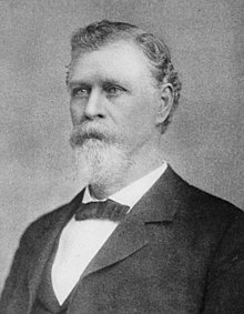 A man with gray hair, beard, and mustache wearing a black jacket and neck tie and a white shirt